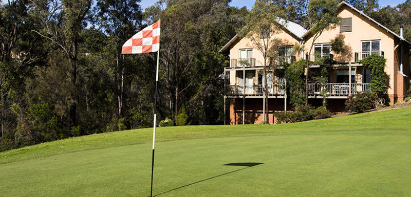 golf green with red and white flag