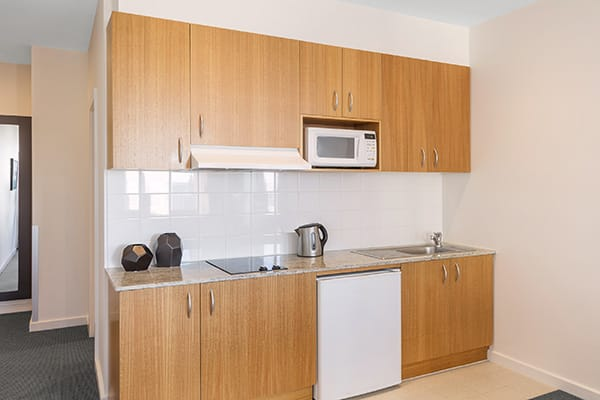 double bed in air conditioned Studio Apartment with microwave and kettle in kitchenette at Oaks on Market hotel in Melbourne city, Victoria, Australia